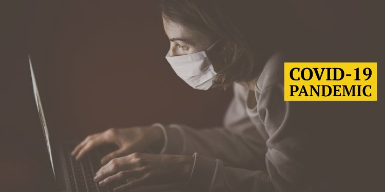 Woman with mask typing on laptop computer