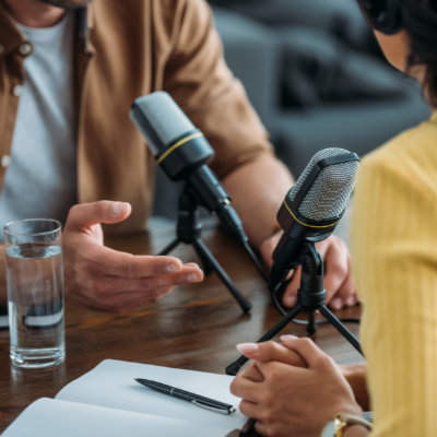 Two people talking in front of podcast microphones while sitting at a table